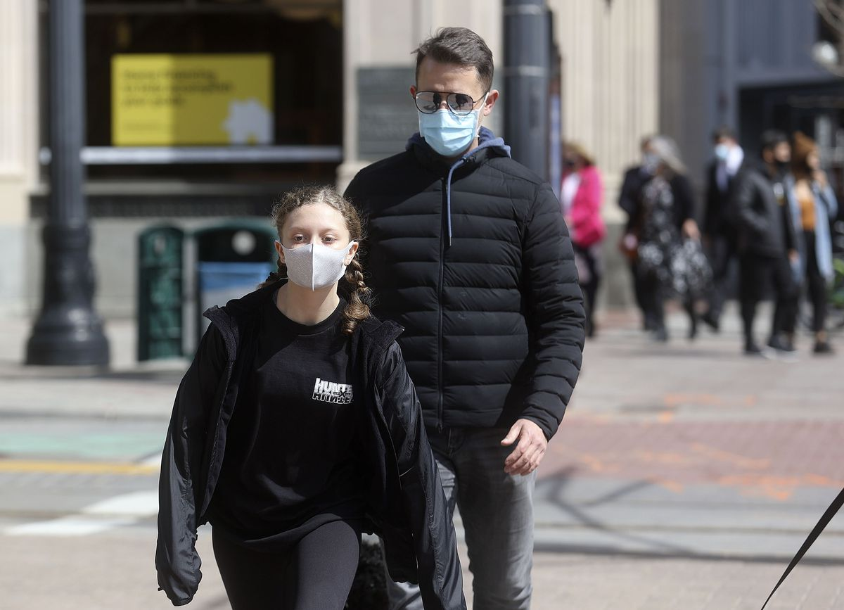 Sophia Cline, left, and Brent Cline wear masks while walking in downtown Salt Lake City on Wednesday, March 24, 2021.