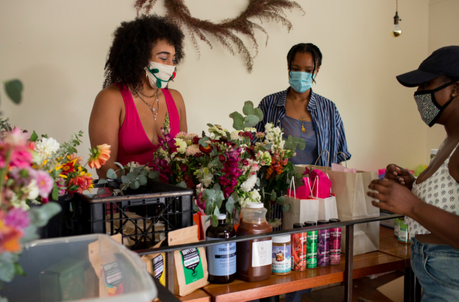 Two people stand in front of a display of drinks and flowers at Love Letters to Black Folks