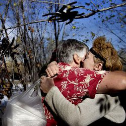 Monica Carlson hugs Ed Snoddy at her camp near the Jordan River in West Valley on Thursday, Nov. 24, 2016. Snoddy gave Carlson a hot turkey dinner, dry socks and his word that he would be back to check on her in a few days.