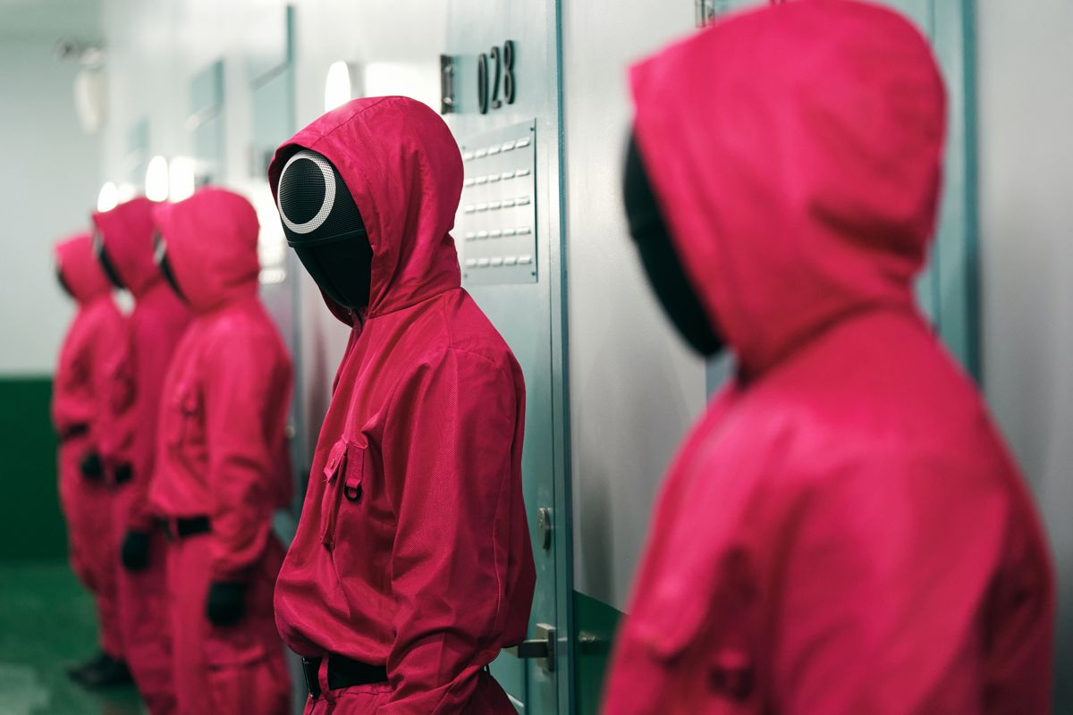 A row of pink-jumpsuited, masked workers from Squid Game