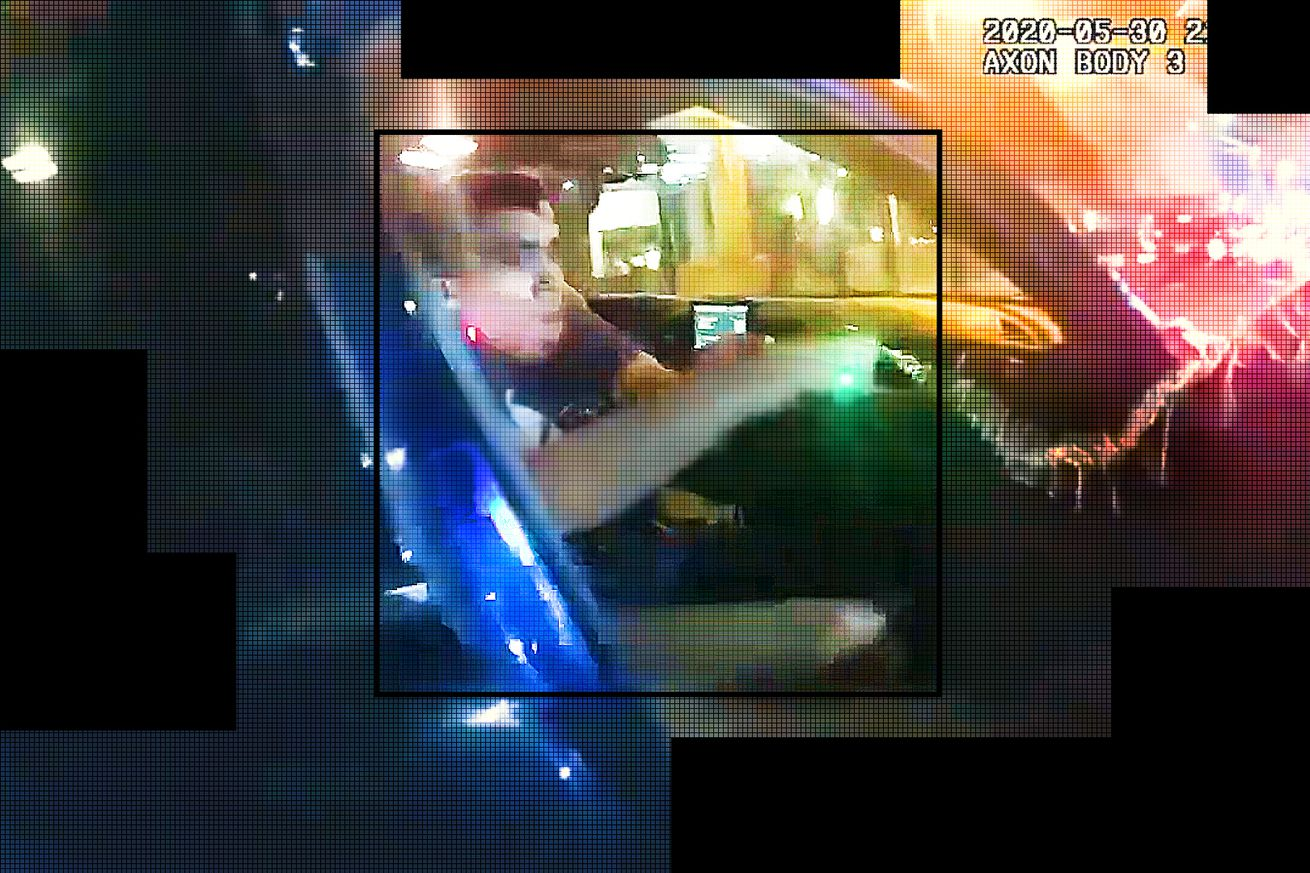 In a still from a police body camera videoclip, we see a man being pulled from a car.