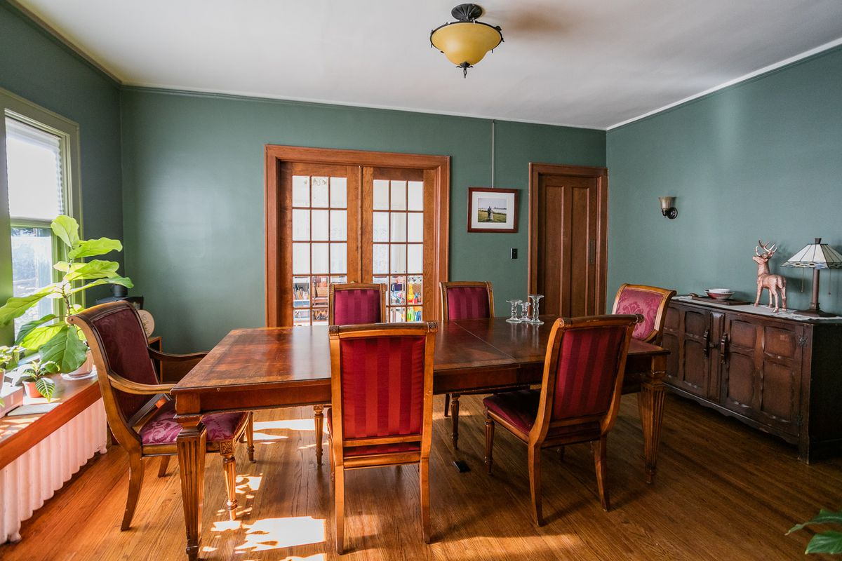 A dining room with a wood table surrounded by six chairs with red felt backs. The walls are painted dark green.