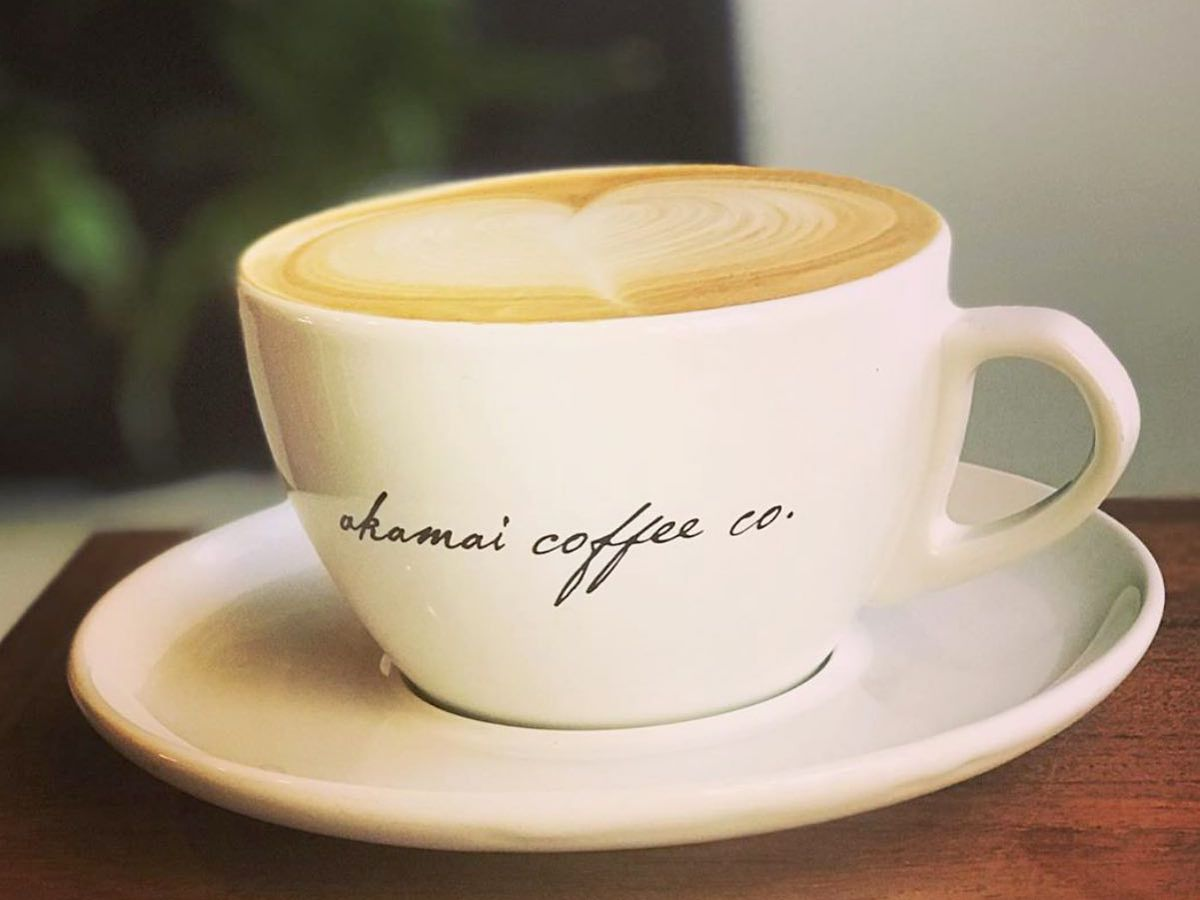 A latte filled to the brim of a coffee mug decorated with the cafe's name in cursive script