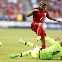 Venezuela's Rupert Quijada (4) kicks the ball under United States defender DeAndre Yedlin (2) during a soccer game at Rio Tinto Stadium in Sandy on Saturday, June 3, 2017. They tied 1-1.