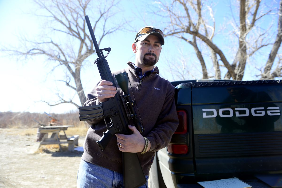Mac Holder, a resident of rural Rocky Ford, CO, shows off his AR-15 with a 30-round clip attached