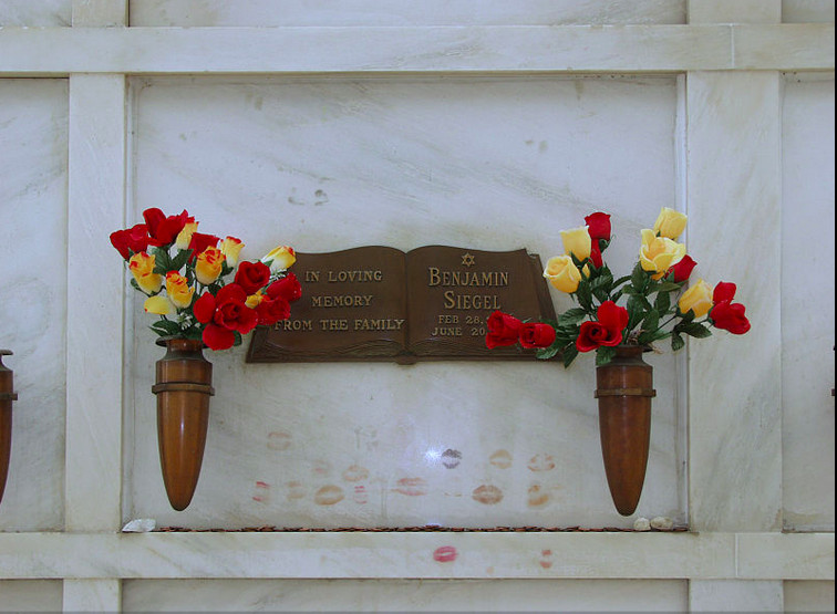 The inside of a mausoleum at the Hollywood Forever cemetery. There is a plaque on the wall that is brown and reads: In loving memory from the family, Benjamin Siegel. There are flowers in vases on a shelf in front of the plaque. There are lipstick kiss ma