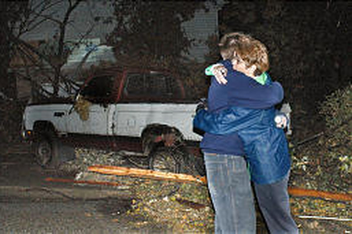 Steve Auten hugs his mother, Shelly, after a tornado swept through Newburgh, Ind., early Sunday. Steve had been a mile and half away with friends when the storm hit and came looking for his parents just as they were looking for him. The tree in the Auten'