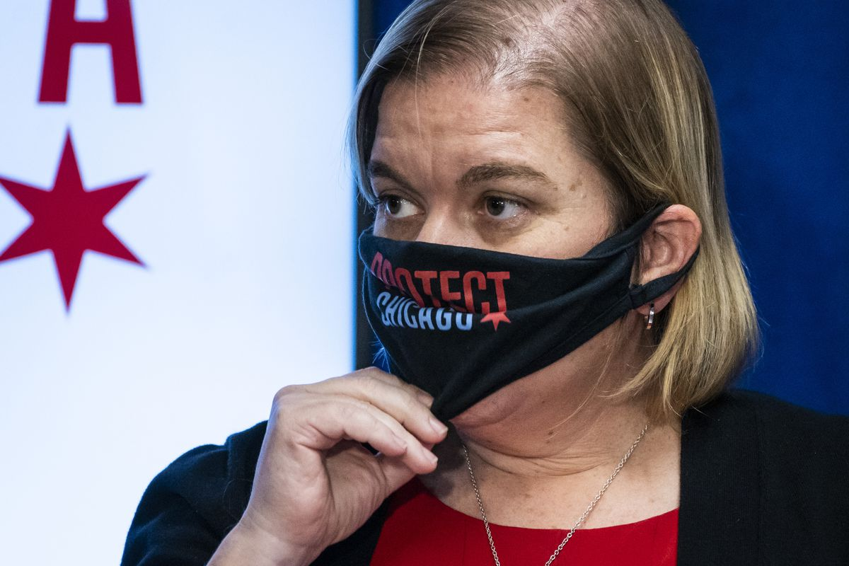 Chicago Public Health Commissioner Dr. Allison Arwady on Tuesday adjusts her face mask as she speaks at a City Hall news conference to announce a return to an indoor mask mandate starting Friday.