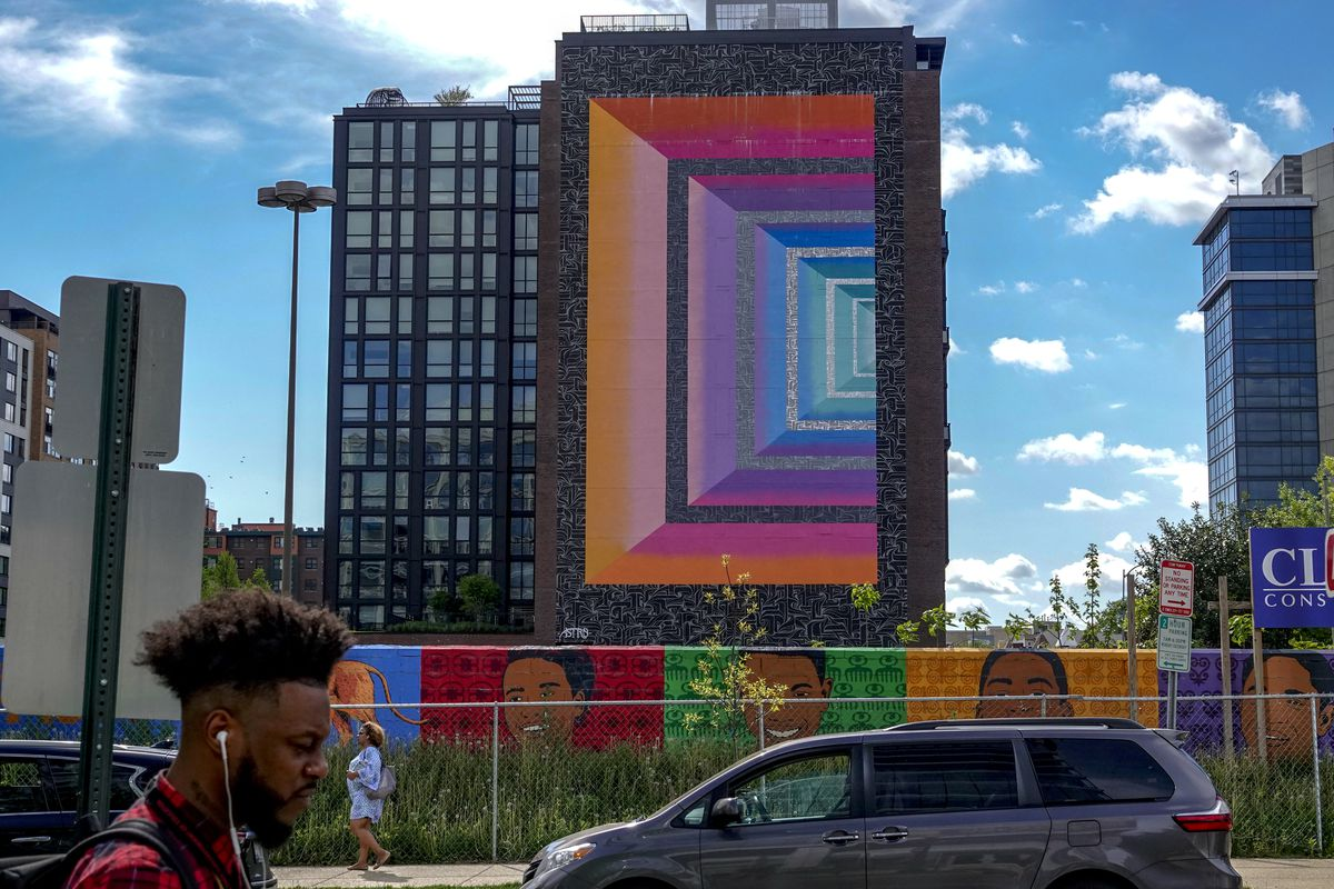 A multicolored mural on a residential building in D.C.'s NoMa neighborhood. The building is in the background of the photo and pedestrians are seen walking on sidewalks in front of it.