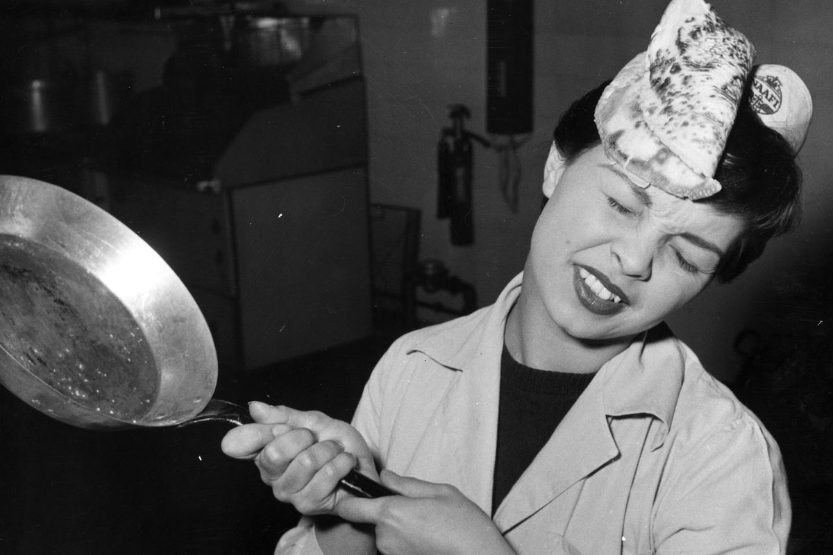 Black and white photo from the '50s depicting a woman flipping a pancake that's escaped the pan and hits her in the face.