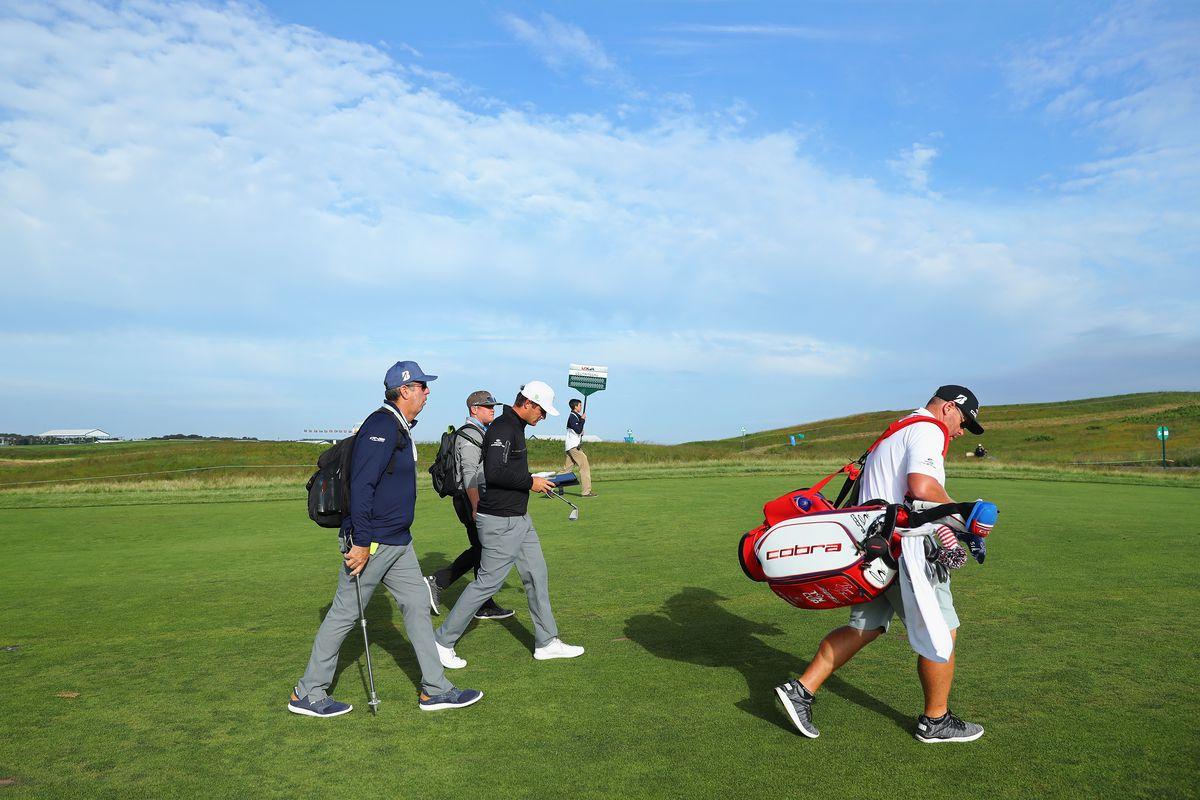 Bryson DeChambeau and his caddie walk during a practice round at Shinnecock Hills Golf Club