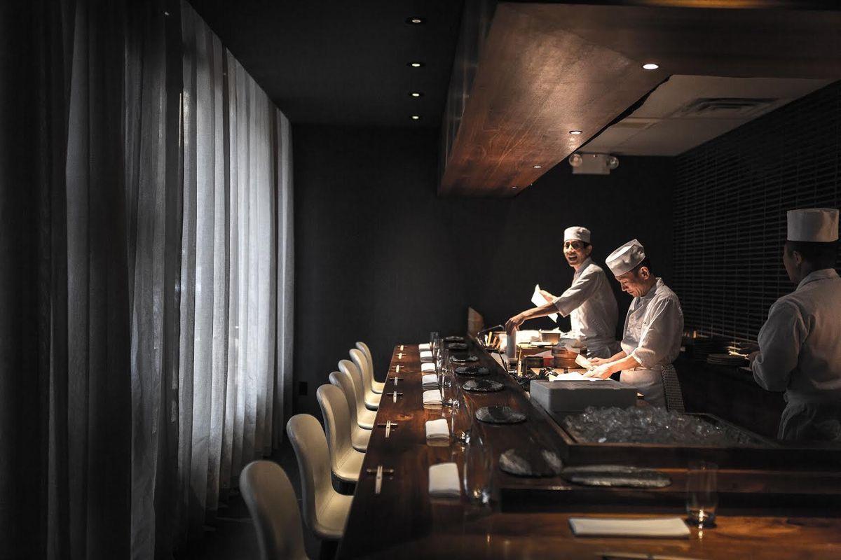 Kosaka chefs stand behind an empty sushi bar, preparing food