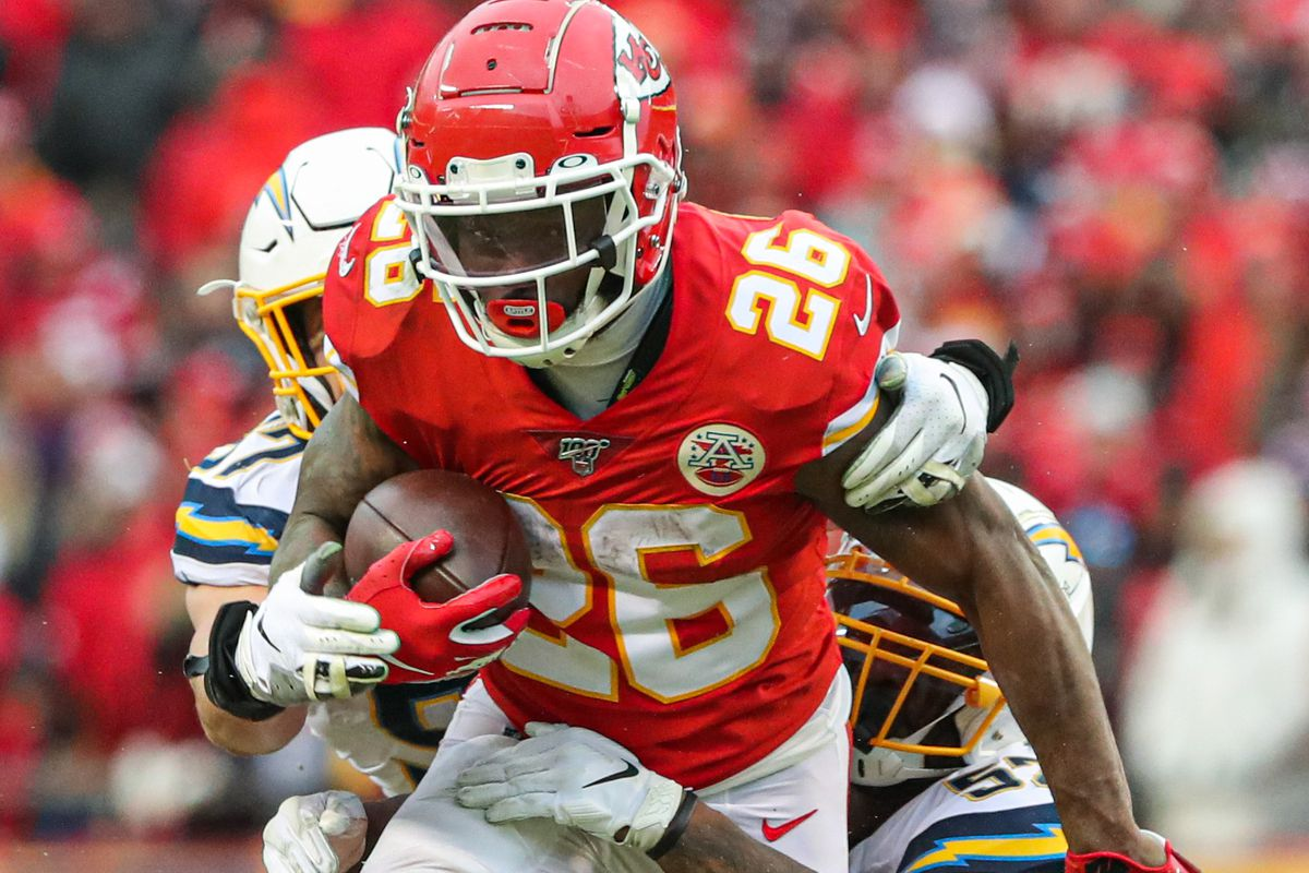Kansas City Chiefs running back Damien Williams (26) is tackled by Los Angeles Chargers middle linebacker Denzel Perryman and defensive end Joey Bosa during the second half at Arrowhead Stadium.