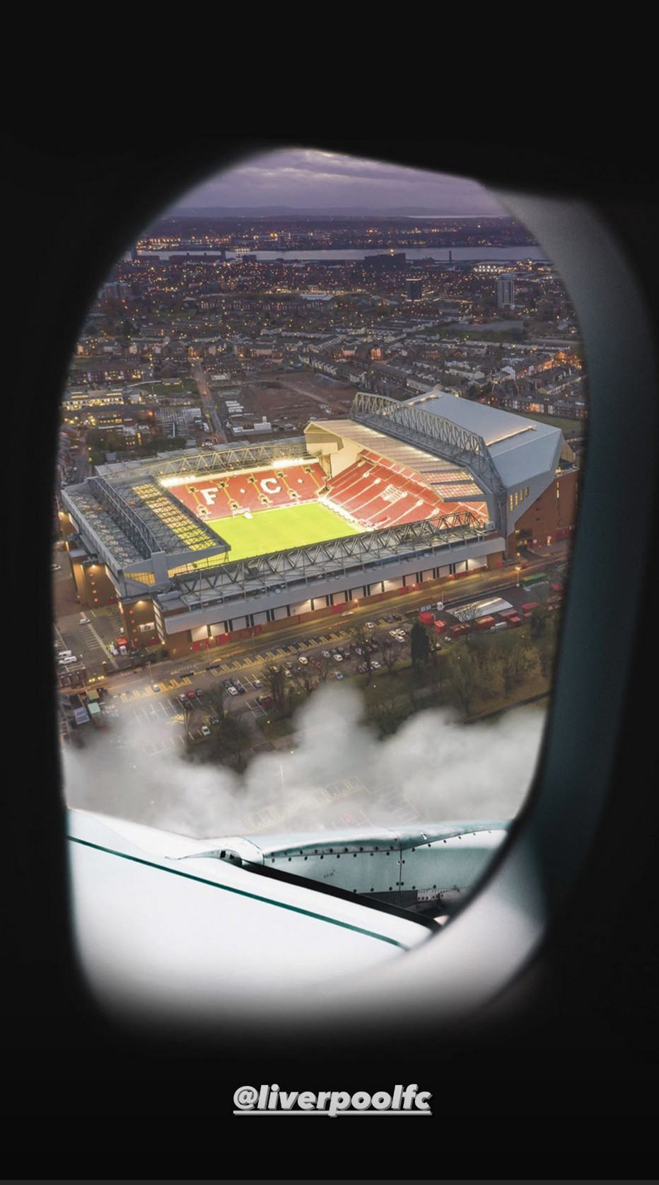 Anfield is captured from a plane window, empty and lit up at night