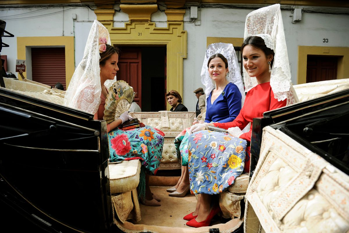 """April 15: Participants sporting traditional """"mantillas"""" (shawls) wait for parading during the XXXIII """"Enganches"""" (Horse-drawn carriages) exhibition at the Real Maestranza bullring in Sevilla, Madrid. (Cristina Quicler/AFP/Getty Images)"""