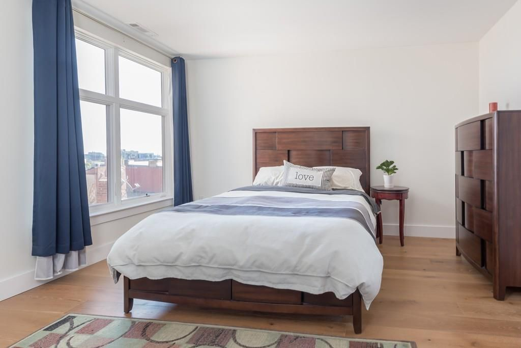 A bedroom with a bed next to a window.