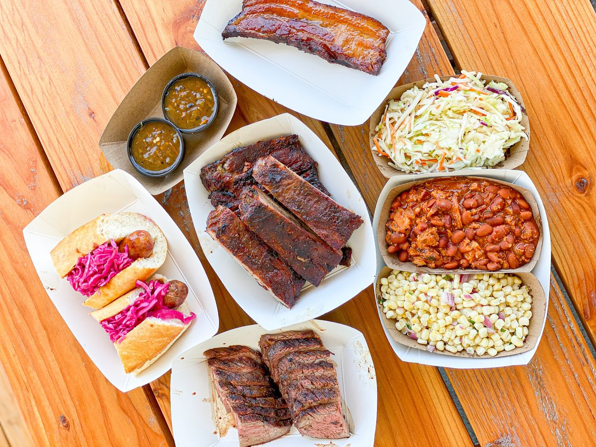 An overhead shot of a wooden table with trays of smoked meat including cut slices of tri-tip, ribs, a sausage, and more.