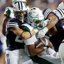 Brigham Young Cougars defensive back Ammon Hannemann (22) makes a tackle on South Florida Bulls running back Jaren Mangham (0) as BYU and USF play a college football game at LaVell Edwards Stadium in Provo on Saturday, Sept. 25, 2021.