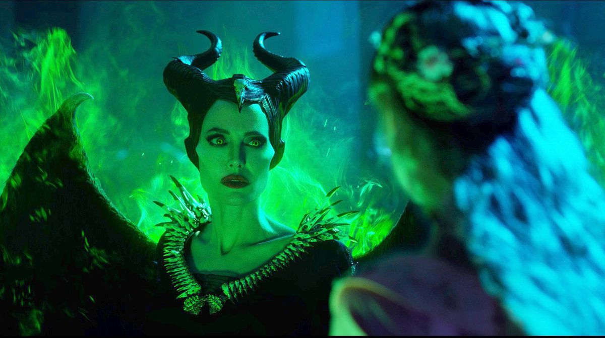 Wreathed in green fire, Maleficent (Jolie) looks wary.