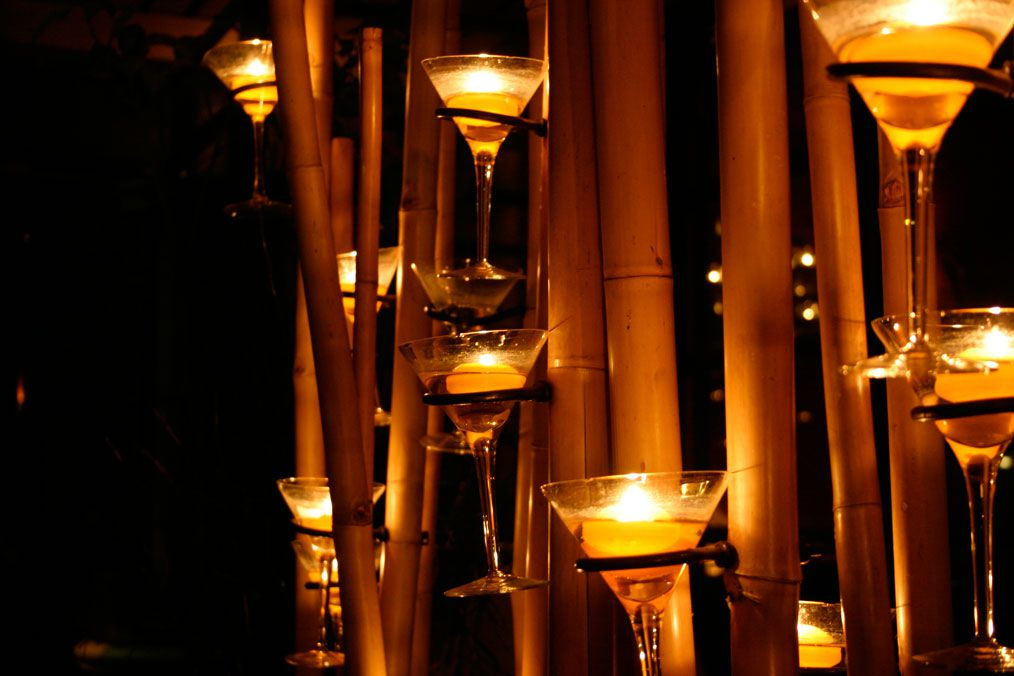 A view of candles inside martini glasses with a bamboo backdrop at Tamarind Tree.