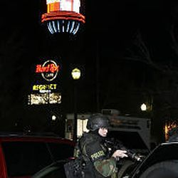 A SWAT team member inspects vehicles at Trolley Square Monday. The mall was evacuated and the surrounding area cleared.
