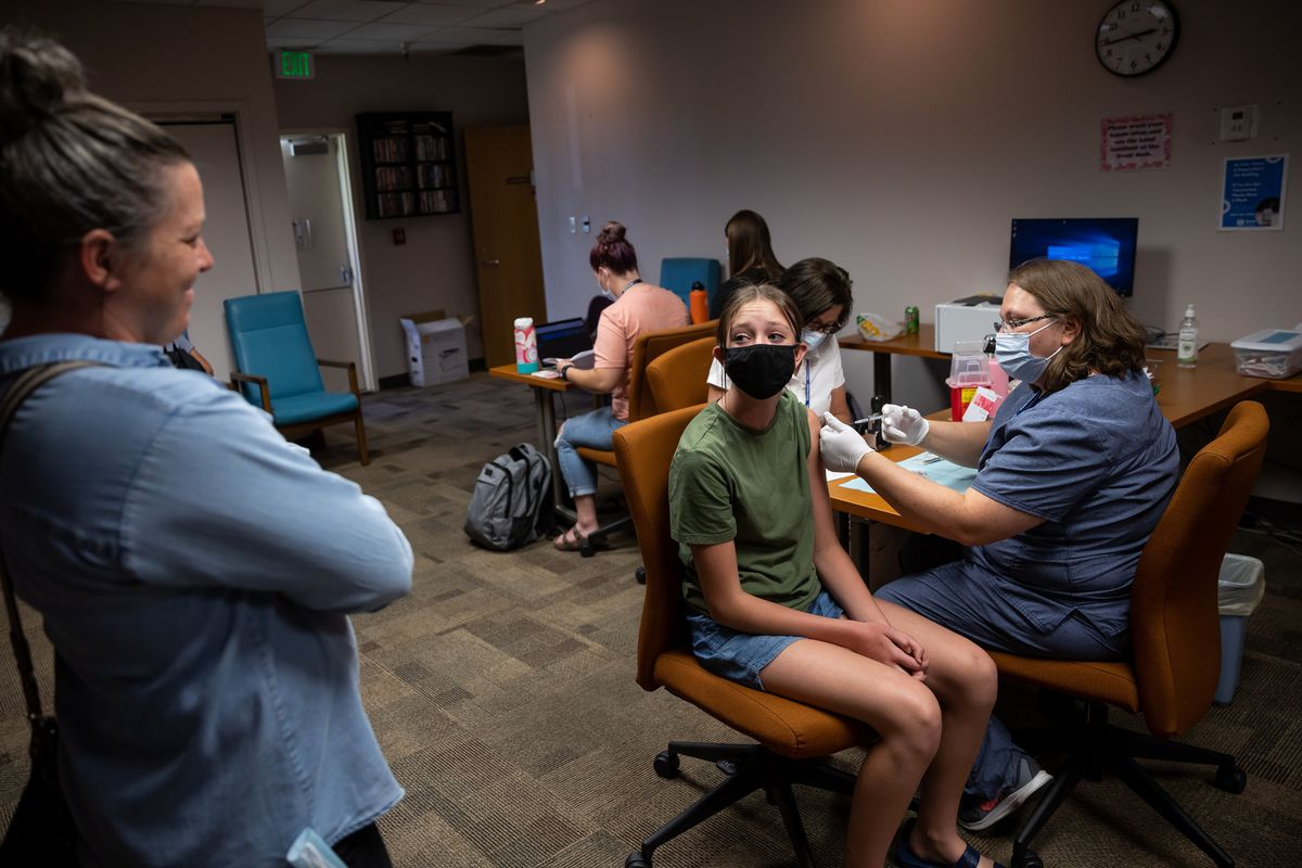 Audrey Rogers, 14, looks back at her mother, Emily Rogers, as she gets her first dose of the Pfizer-BioNTech COVID-19 vaccine from nurse Clarece Glanville at the Central Davis Senior Activity Center in Kaysville on Tuesday, July 6, 2021.