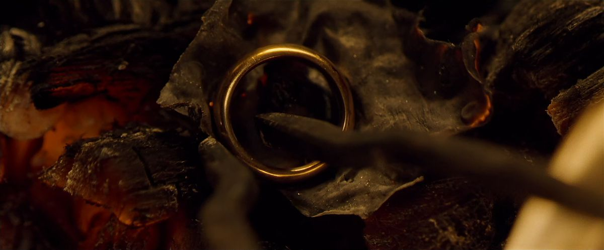 Tongs reach into the ashes of a fire to grasp the One Ring in The Fellowship of the Ring.