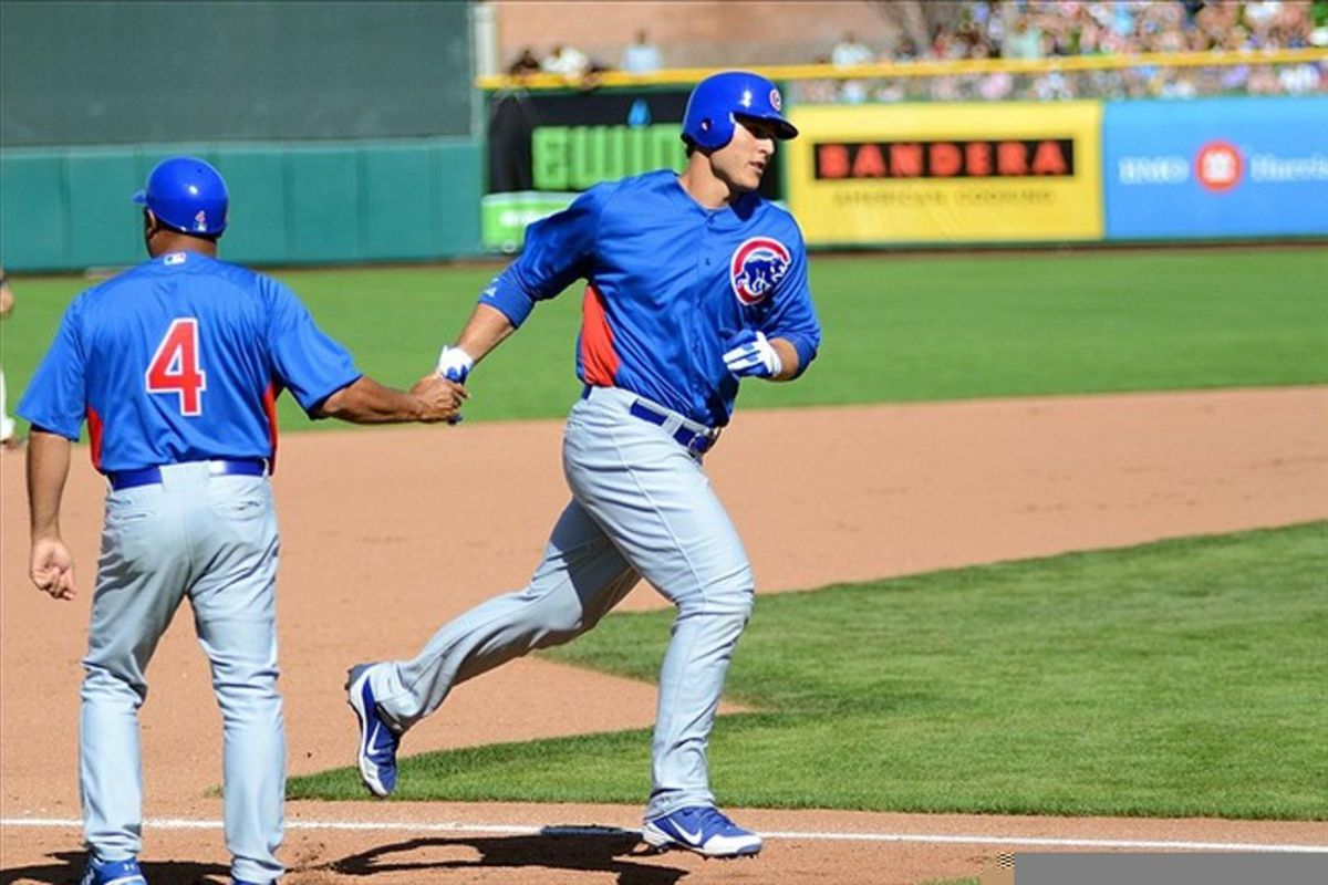 Scottsdale, AZ, USA; Chicago Cubs first baseman Anthony Rizzo is congratulated by third base coach Pat Listach after hitting a solo home run against the San Francisco Giants at Scottsdale Stadium. Credit: Jake Roth-US PRESSWIRE