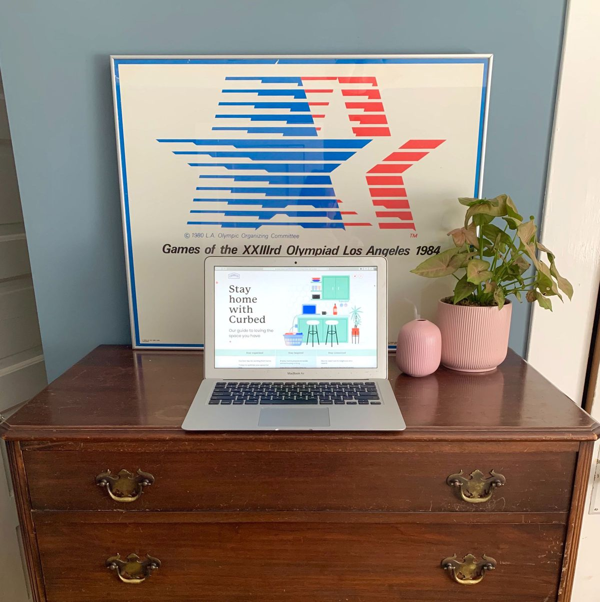 A laptop sits on a wooden chest, which also has a pink candle and planter.