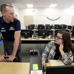 Mike Ashton, a Snow College admissions adviser, talks to Angela Rivas as Rivas works on her applications to the University of Utah, Washington State and Colorado State during Utah College Application Week at Hillcrest High School in Midvale on Tuesday, Oct. 22, 2019.