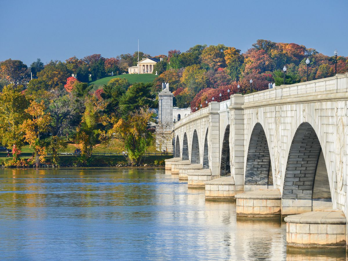 The Arlington Memorial Bridge in Washington D.C. The bridge spans over a body of water and is connected to an area with many trees that have multicolored leaves.