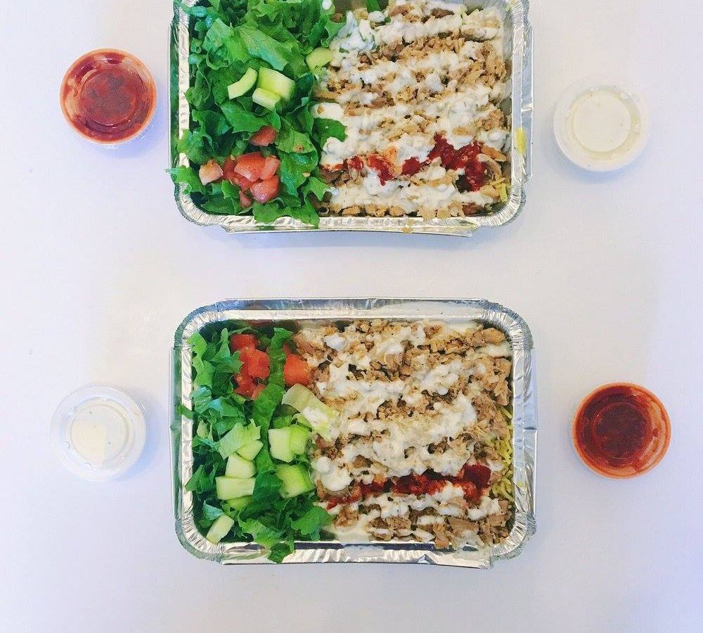 Two tin containers full of rice, chicken, sausages, and salads