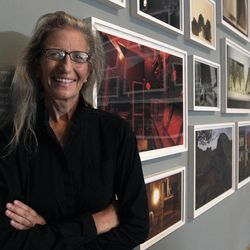 """Annie Leibovitz stands near some of her work before the opening of her exhibition at the Wexner Center for the Arts Friday, Sept. 21, 2012, in Columbus, Ohio. Leibovitz's exhibition features work from her """"Master Set,"""" an authoritative edition of 156 images."""