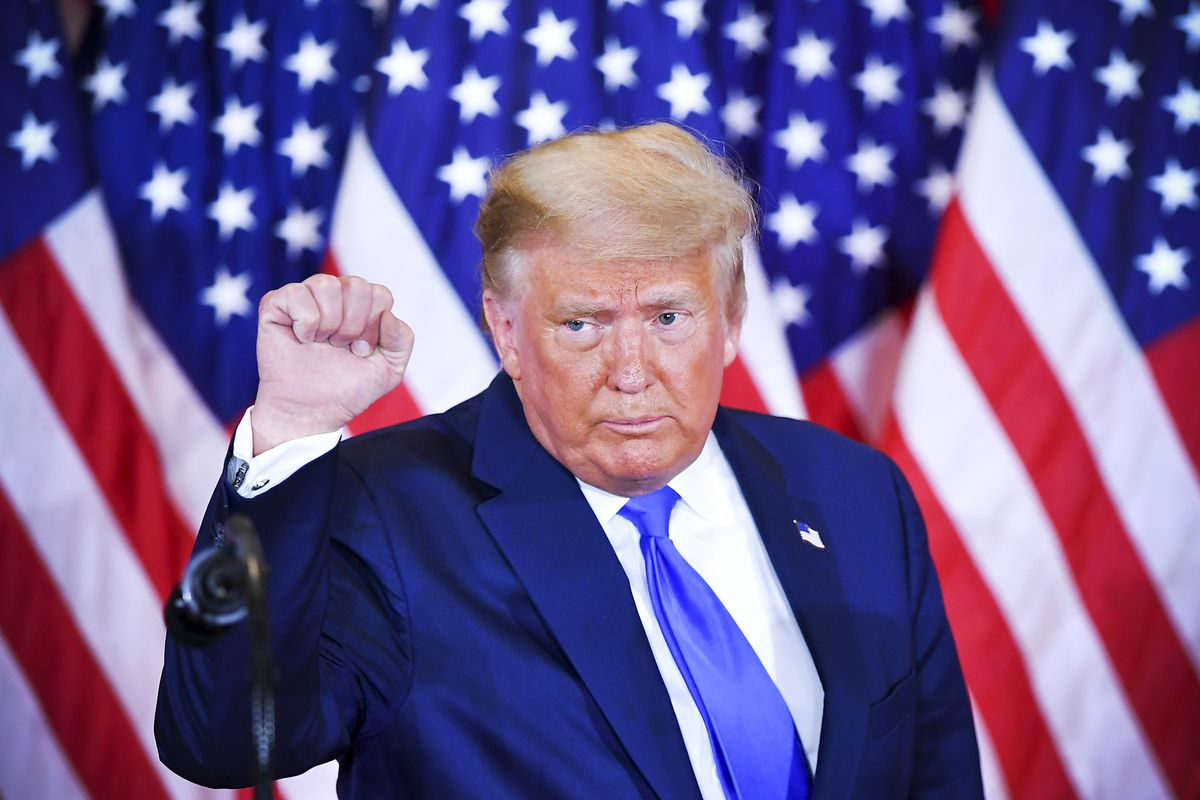 President Donald Trump, standing in front of American flags, raises his hand in a fist.