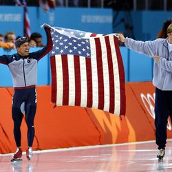 USA's Derek Parra and coach Bart Schouten hold the American flag between them after Parra set a world record to win the gold medal in the 1,500 meter speedskating event on Tuesday, Feb. 19, 2002.