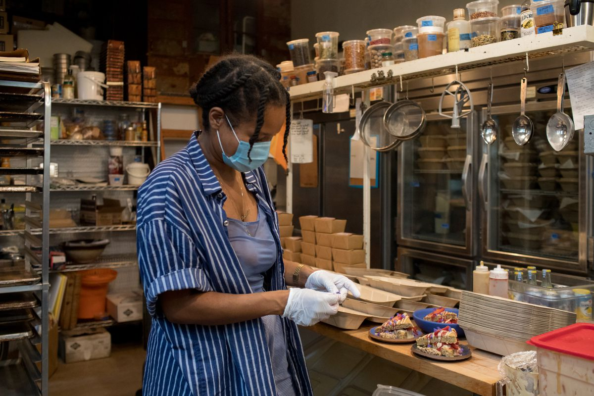 Woman wearing mask and gloves closes a takeout container while inside a restaurant kitchen.