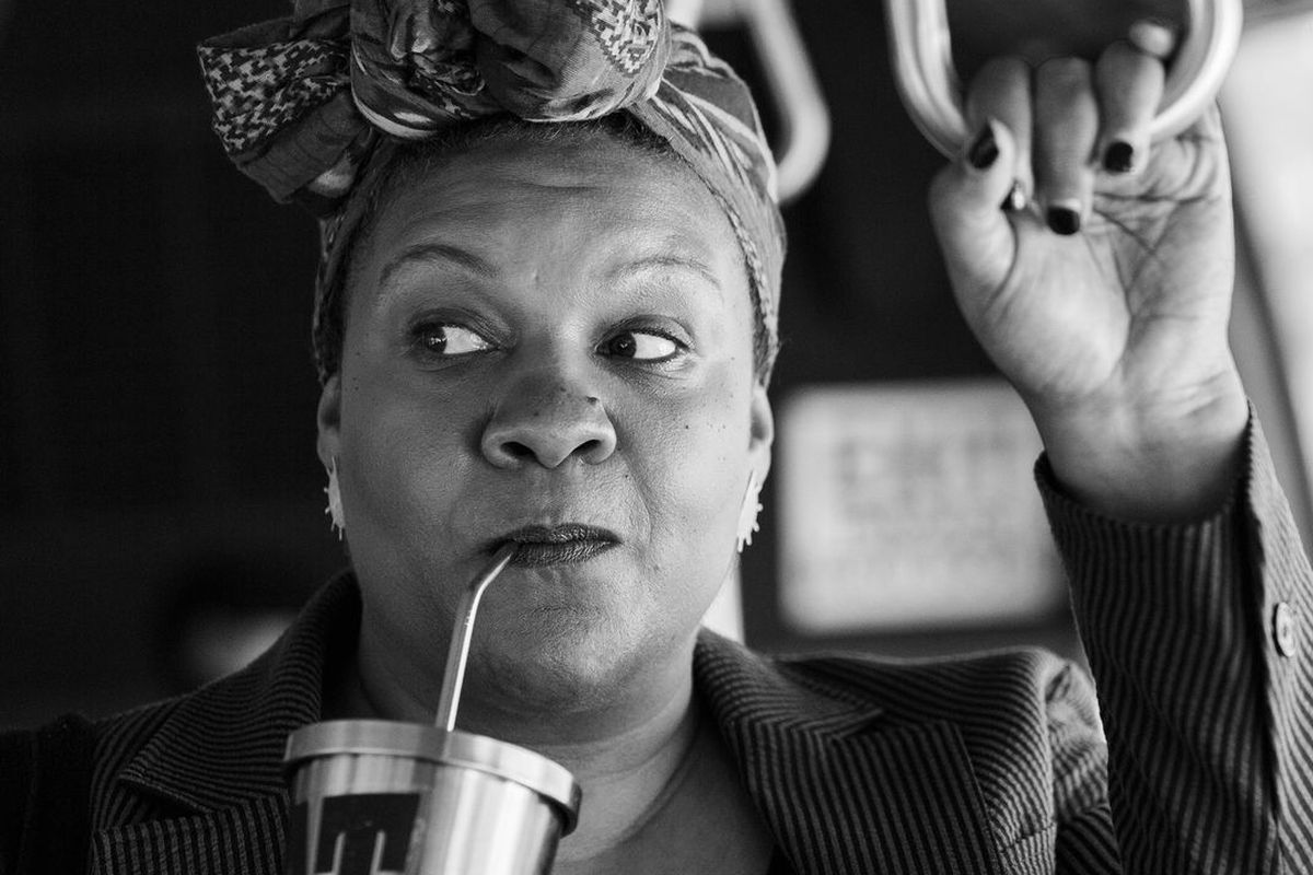 Radha Blank in a black-and-white image, sipping on a cup while on a bus.