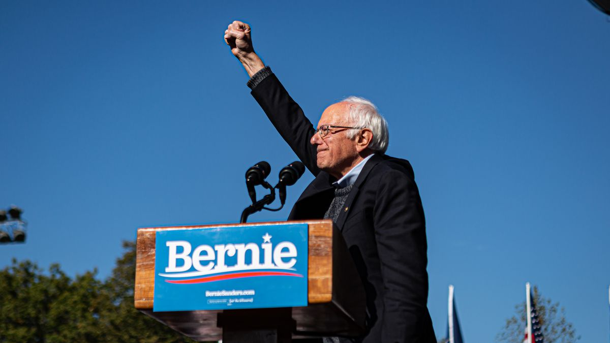 Bernie Sanders stands at a podium with his fist in the air.