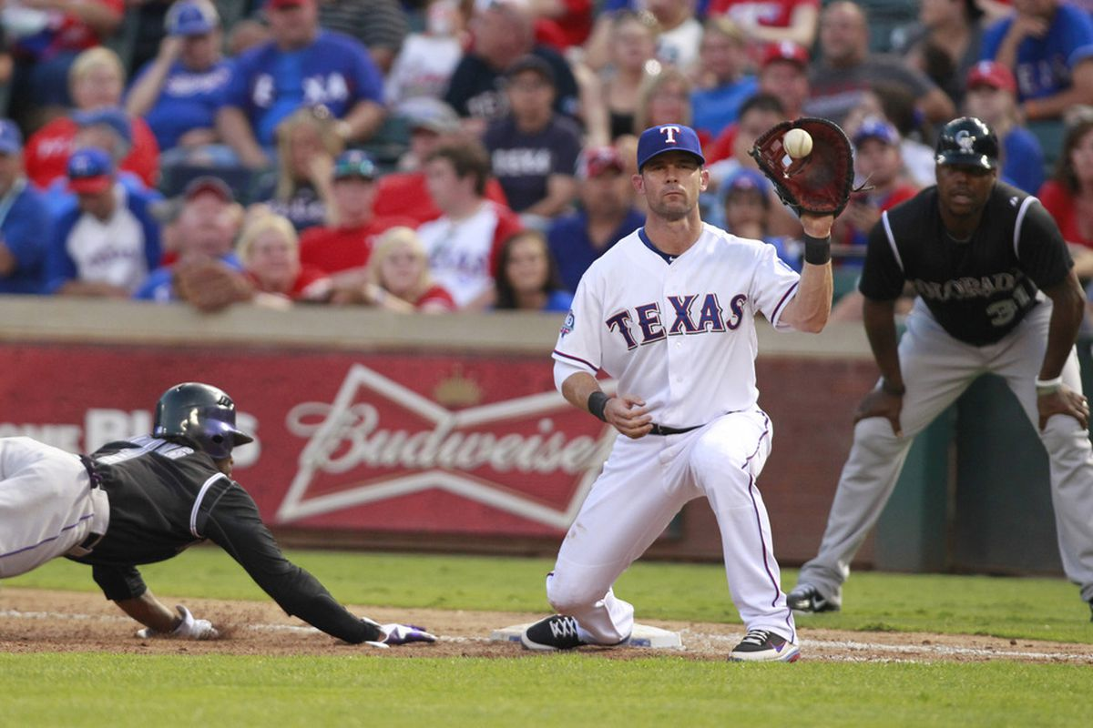 Jun 24, 2012; Arlington, TX, USA; Texas Rangers first baseman Michael Young (10) catches a pick off attempt during the game against the Colorado Rockies at Rangers Ballpark. The Rangers beat the Rockies 4-2. Mandatory Credit: Tim Heitman-US PRESSWIRE