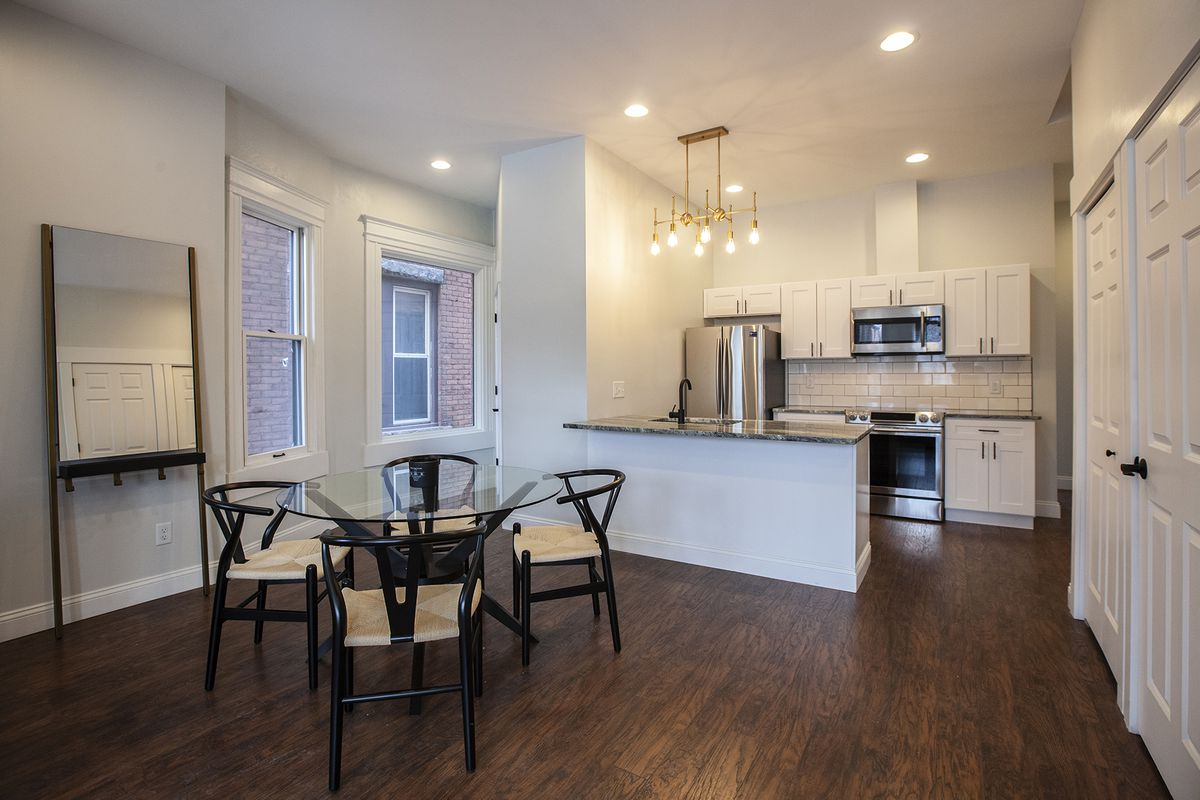 A combined dining room and kitchen. All the walls are white and there's hardwood floors.