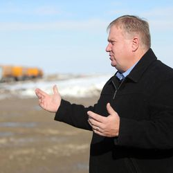 Jim Russell, assistant director of the Utah Division of Facilities Construction and Management, discusses construction of the new prison as crews build a temporary road to access the site, seen behind him, in Salt Lake City on Wednesday, Dec. 28, 2016.