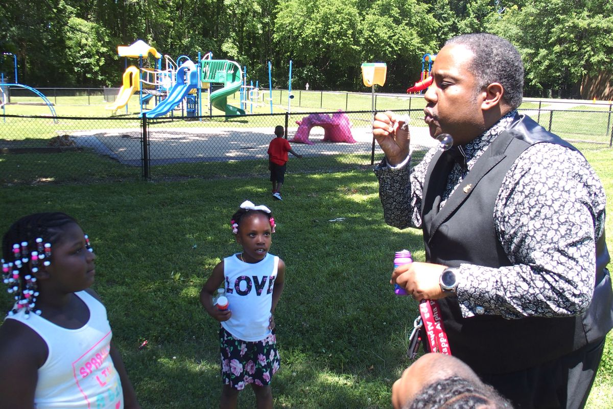 Principal Antonio Harvey shows kindergarteners how to blow bubbles during a graduation celebration at Hawkins Mill Elementary School in the Frayser community of Memphis.