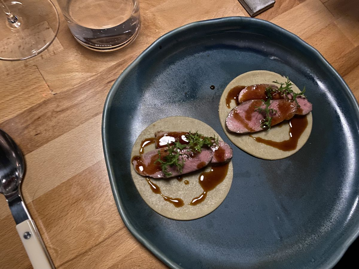 An overhead photograph of what appears to be two tacos filled with slices of duck and a dark glaze on a dark-colored plate