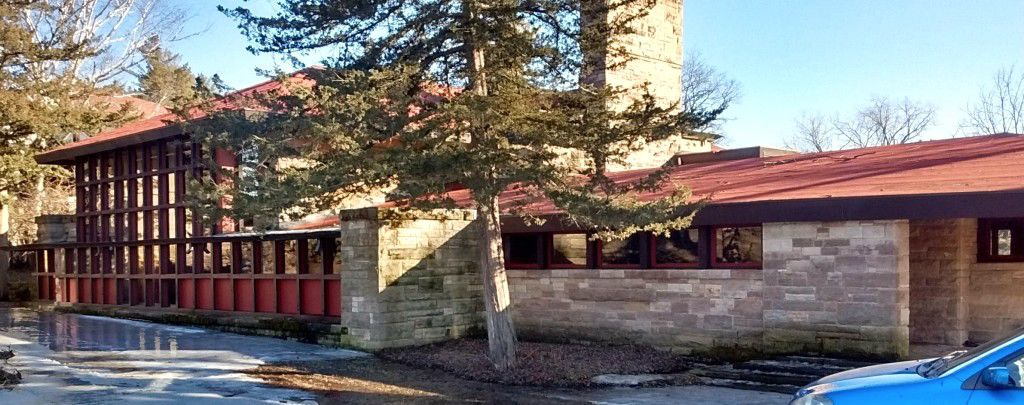 The exterior of Frank Lloyd Wright's Hillside Studio and Theater. The facade is tan brick with a red brick and red decorative details.