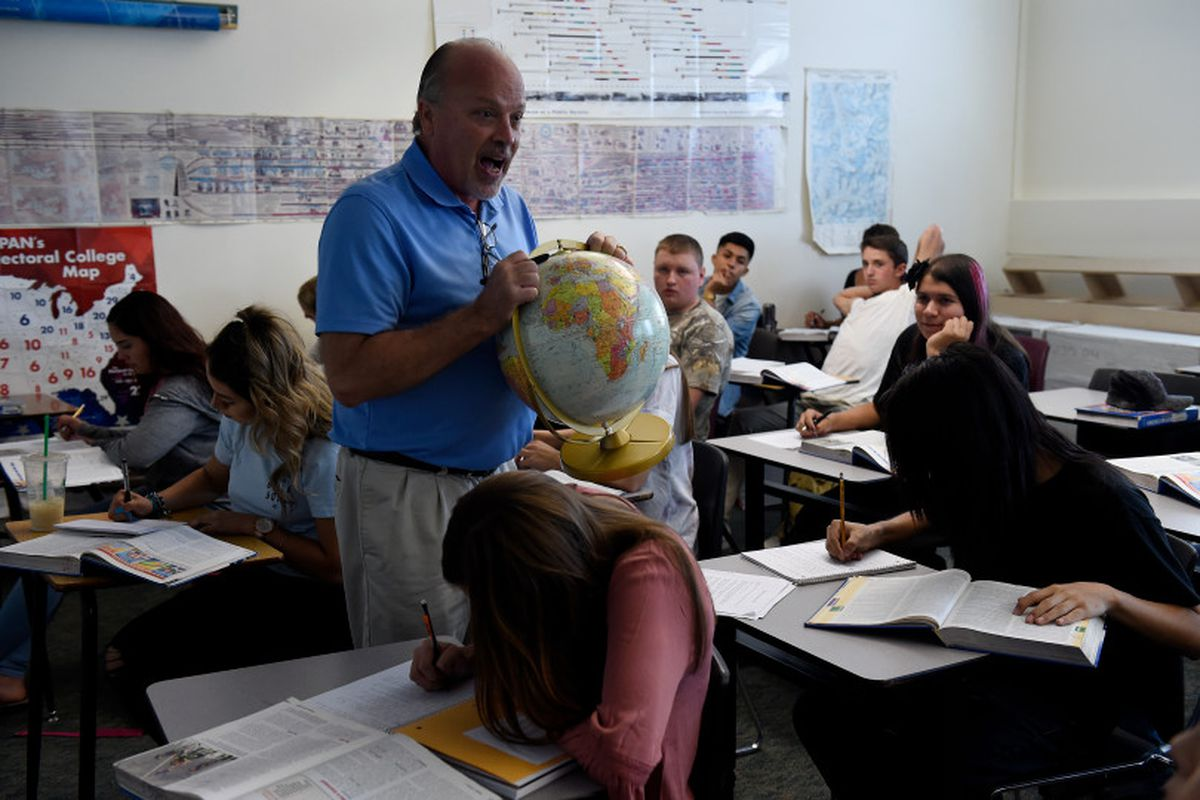 Tom Ritter holds up a globe as he teaches his students during a Political Science class in August of 2017 at Brighton High School. (Photo by Seth McConnell/The Denver Post)