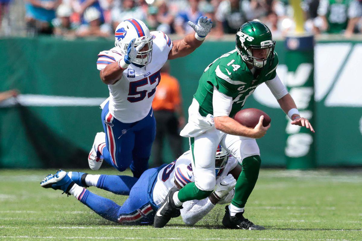 New York Jets quarterback Sam Darnold breaks a tackle as Buffalo Bills outside linebacker Lorenzo Alexander dives during the first half at MetLife Stadium.
