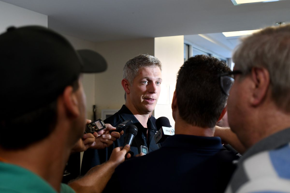 Mike Elias in the middle of a scrum of reporters.