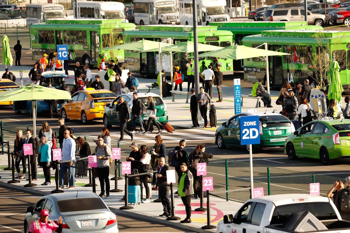 Passengers at LAX use the new passenger pickup lot for Uber, Lyft, and taxis