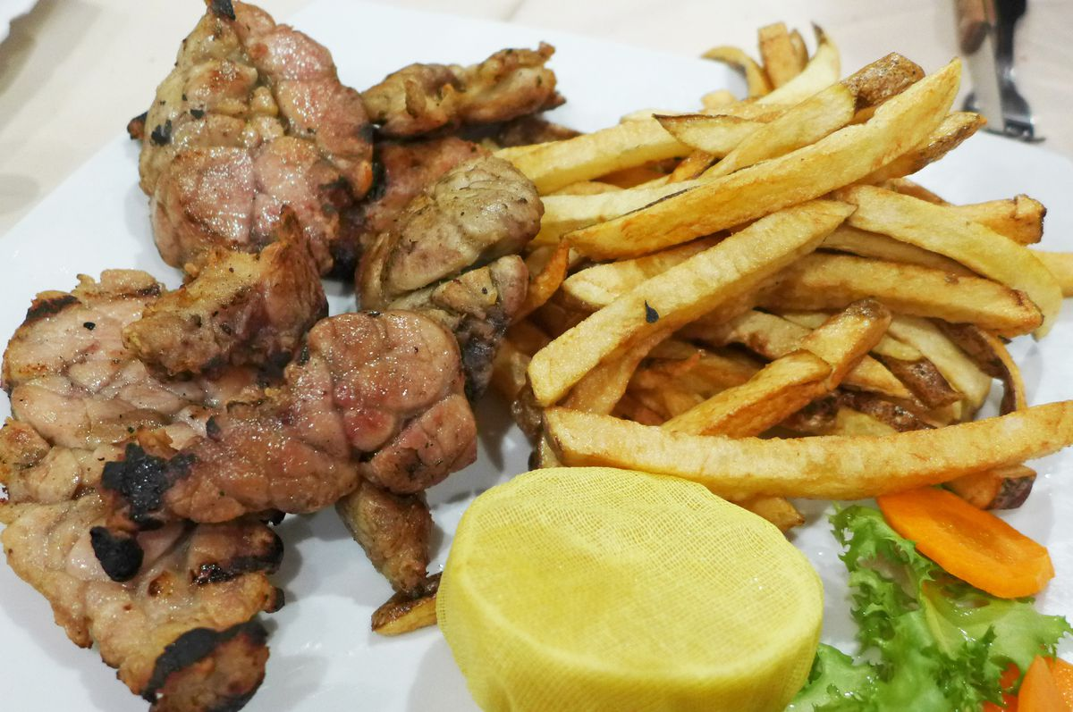 Amorphous and beige grilled glands with fries on the side.