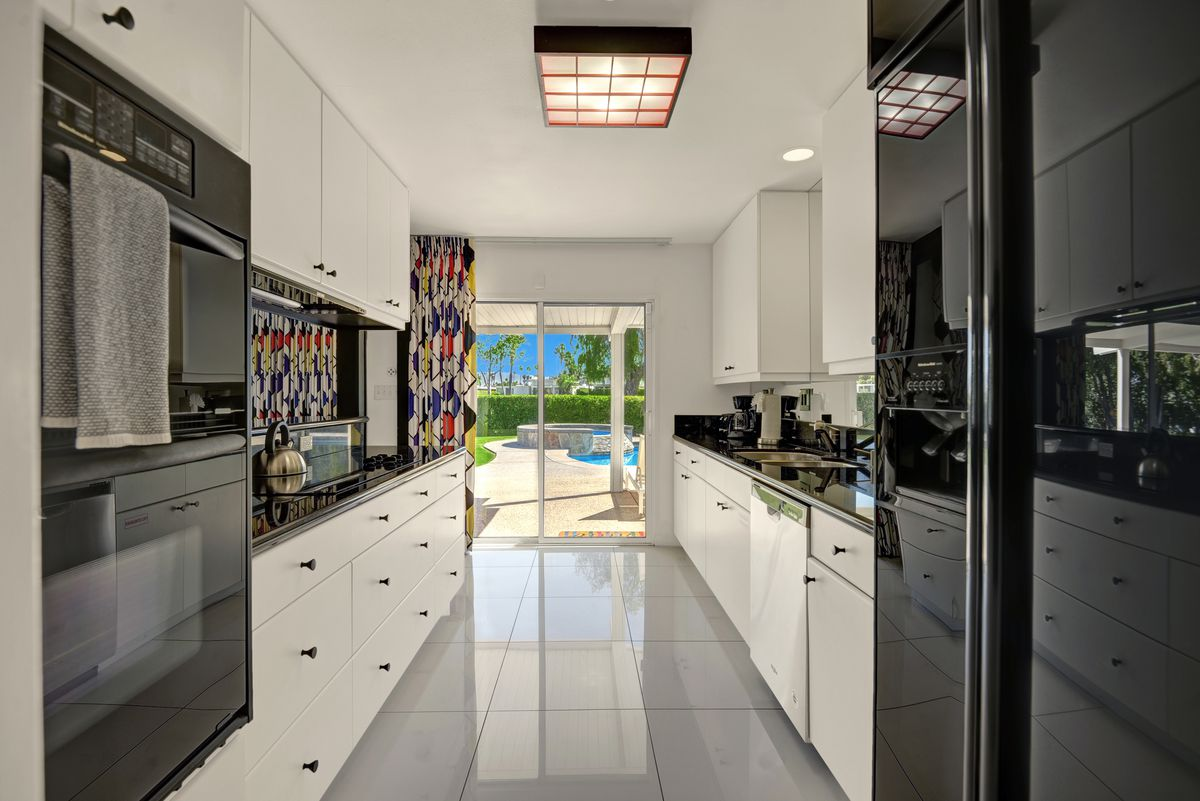 A long, narrow kitchen features white cabinets and black countertops.